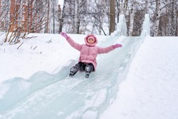 A young woman in a pink down jacket is riding in a city park on an ice slide without a sled