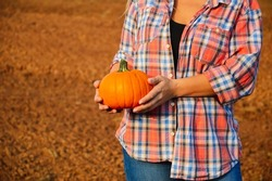 A young woman in a plaid shirt and jeans holds an orange pumpkin in her hands on the background of the field. Harvesting in autumn at the farm. Preparing for Halloween. Growing organic vegetables