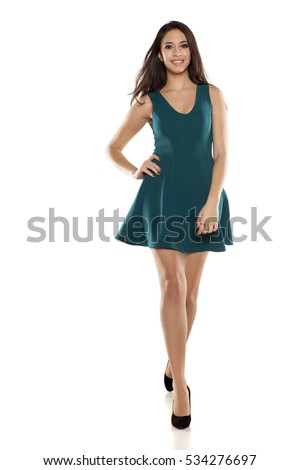 a young woman in a short turquoise dress walking on white background