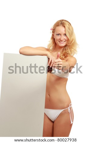 A young woman in a swimsuit with a blank, showing ok, isolated on white