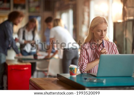 A young woman in a working atmosphere in the office is focused on the work on a laptop. Employees, office, work