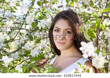 A young woman in an apple orchard at the time of full bloom.