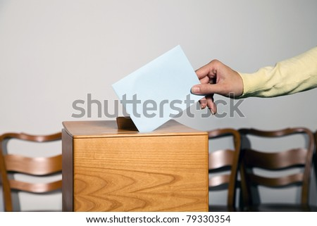 A young woman in an election shall deliver their vote. Ballot at the polling station.