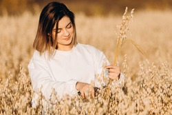 A young woman in an oat field holds a bunch of ripe ears of corn.