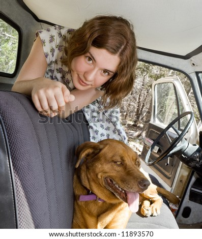A young woman in an old pickup truck with her beloved dog