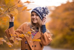 A young woman in an orange fashion coat and a funny cap is walking through the forest.