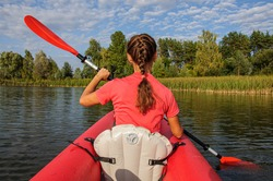 A young woman in bright clothes floats on a red kayak on the river. Ukraine