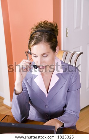 A young woman in business suit talking on a headset working from home