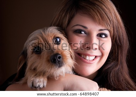 A young woman in her 20s holds a cute mixed breed beagle yorkshire terrier dog.