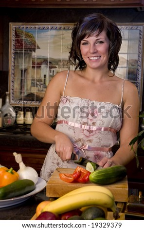 A young woman in the kitchen cutting vegetables
