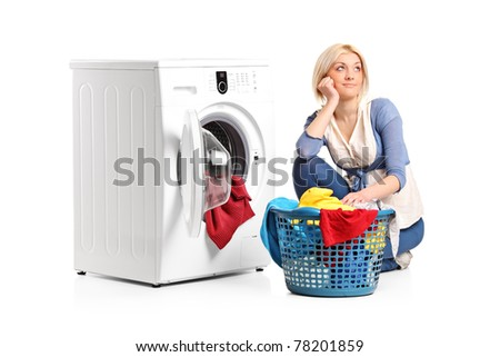 A young woman in thoughts with clothes seated next to a washing machine isolated on white background