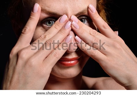 A young woman is covering her face with her hands. She is smiling and looking through the fingers.