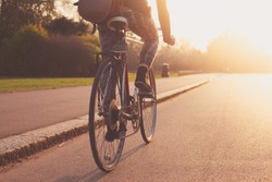 A young woman is cycling into the sunset in the park
