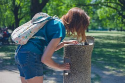 A young woman is drinking from a water fountain in a park on a sunny day in the summer