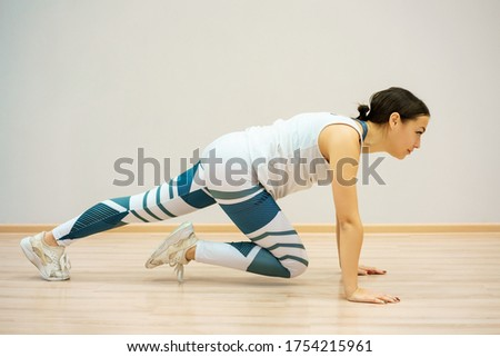 A young woman is engaged in fitness at home on the blue Mat , in sportswear. Training and stretching at home
