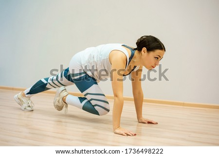 A young woman is engaged in fitness at home on the Mat.
