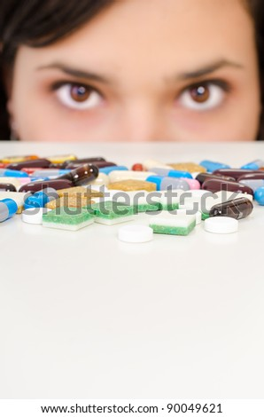 A young woman is hiding behind a table with drugs