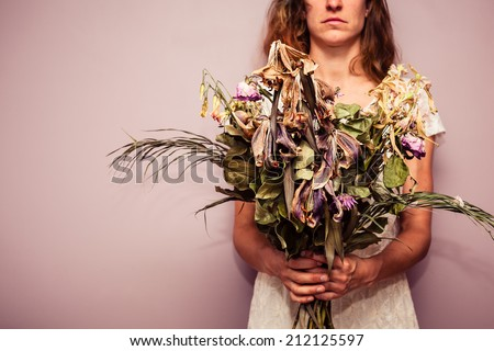 A young woman is holding a bouquet of dead flowers