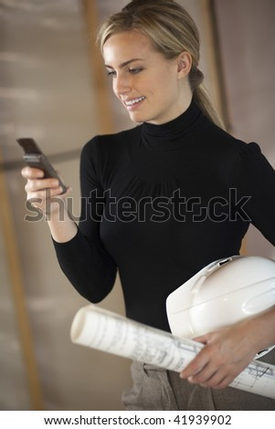 A young woman is holding a cell phone, a hardhat, and blueprints.  She is smiling and looking at the phone.  Vertically framed shot.