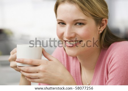 A young woman is holding a coffee cup while smiling at the camera.  Horizontal shot.