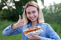 A young woman is holding a large burger. The woman smiles and shows her thumbs up. Unhealthy food, heavy food.