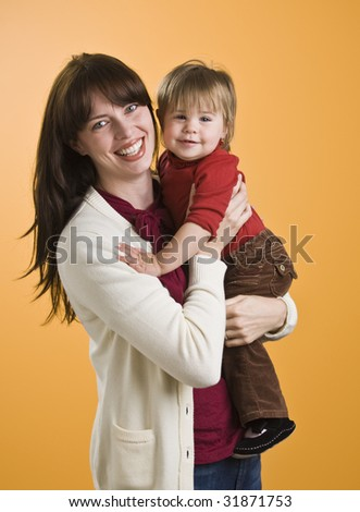 A young woman is holding a toddler and smiling at the camera.  Vertically framed shot.