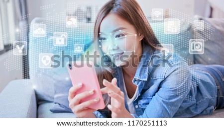 A young woman is holding smart phone with scanning facial recognition lying on sofa.