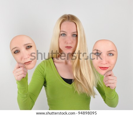 A young woman is holding two mask of herself. One is happy and the other is sad or depressed. use it for a makeover or self esteem concept.