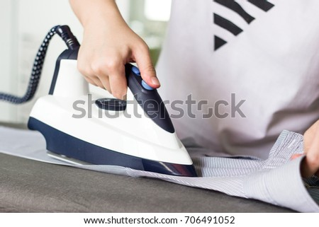 A young woman is ironing the shirt on the ironing board at home. Focus on hand. #706491052