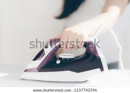 A young woman is ironing the shirt on the ironing board at home. Focus on hand and shirt's button.girl's hands iron clothes iron #1237742596
