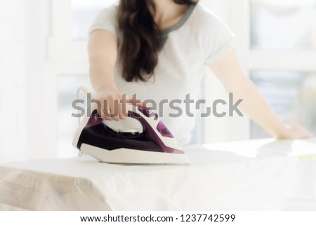 A young woman is ironing the shirt on the ironing board at home. Focus on hand and shirt's button.girl's hands iron clothes iron #1237742599