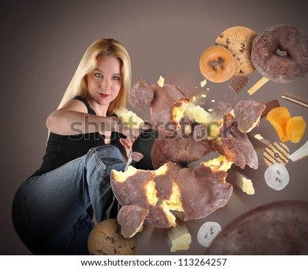 A young woman is kicking a donut into pieces on a brown background within an assortment of junk food. There are cookies, chips and ice cream. Use it for a diet or nutrition concept.