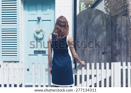 A young woman is looking at a little house with a blue door