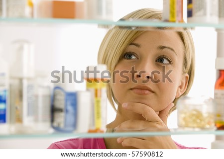 A young woman is looking through her medicine cabinet. Horizontal shot. - stock photo
