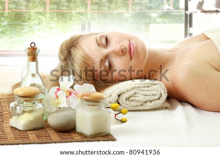 A young woman is lying during a spa treatment on a towel - on white background
