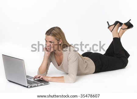 A young woman is lying on the floor and working on a laptop.  She is smiling and looking at the screen.  Horizontally framed shot.