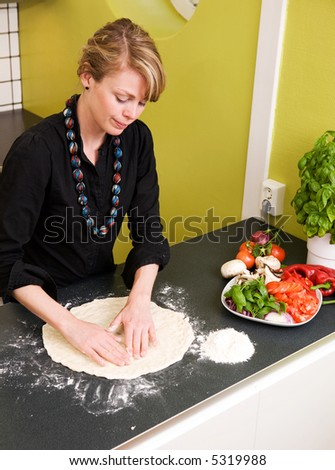 A young woman is making pizza dough on the kitchen counter at home in her apartment - viewed from above.