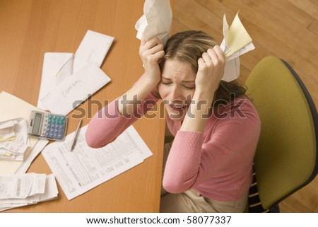 A young woman is paying bills at her desk and has her eyes closed from stress.  Horizontal shot.