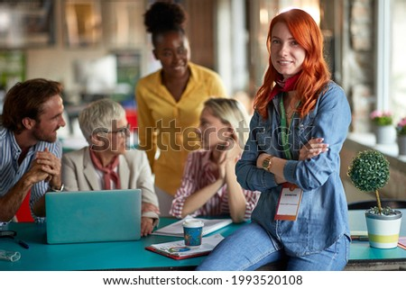 A young woman is posing for a photo while enjoying company of her colleagues in a relaxed atmosphere in the office. Employees, office, work