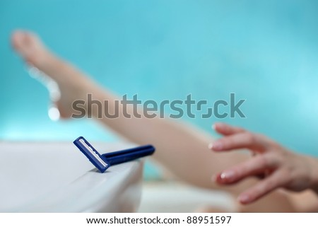 A young woman is reaching for the razor to shave her legs.