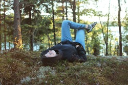 A young woman is resting on the shore of Lake Ladoga. The girl lies with her legs crossed on the reindeer moss. Hike through the Ladoga skerries. Rest in the forest