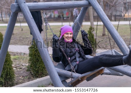 A young woman is riding on a wooden swing smiling on a sunny autumn day #1553147726