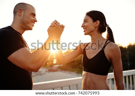 A young woman is shaking the arm of her personal trainer.