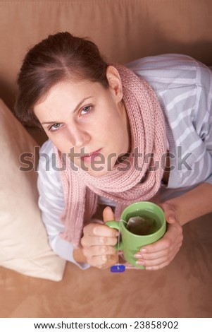 A young woman is sick. She is lying on the couch and is sneezing. She has a tea in her hand.