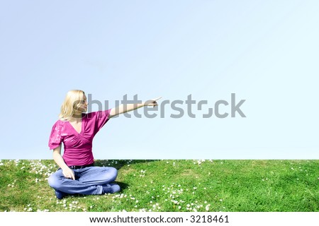 a young woman is sitting on a green meadow and show something