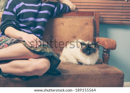 A young woman is sitting on a sofa with her cat