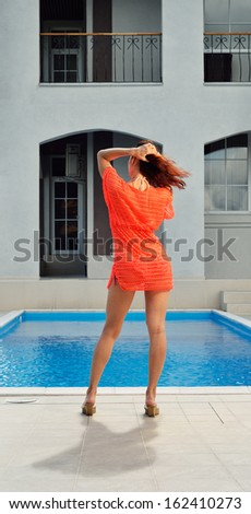 A young woman is standing at the outdoor swimming pool in the yard of her house.
