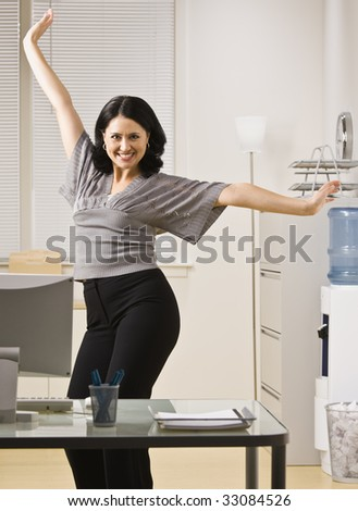A young woman is standing in an office and striking a pose.  She is smilling at the camera.  Vertically framed shot.