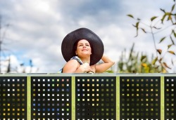 a young woman is standing next to Perforated Metal Fence
