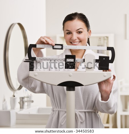 A young woman is standing on a bathroom scale and checking her weight.  She is smiling at the camera.  Square framed shot.